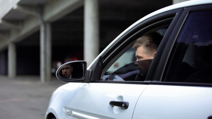Young man spying sitting in car, private information, detective research, mafia - fototapety na wymiar