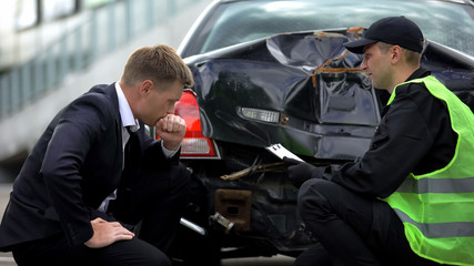 Insurance company agent writing car damage report with driver after accident