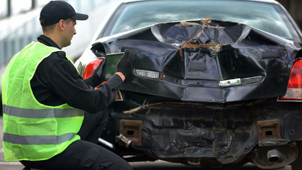 Policeman taking photos of car damage using tablet PC, online accident report