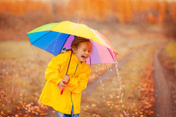 Happy girl with rainbow umbrella in autumn park
