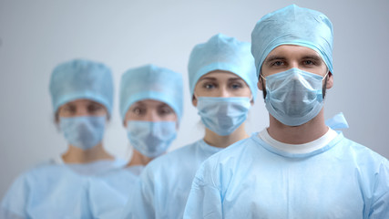 Professional surgeon team in mask and uniform looking at camera, hospital work