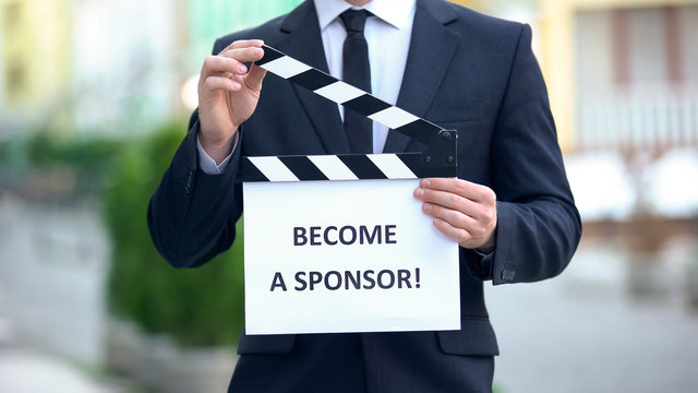 Become a sponsor phrase on clapperboard in hands of producer, independent movie
