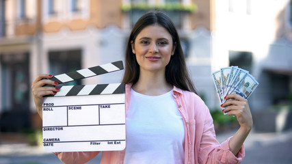 Smiling woman holding clapperboard and bunch of dollars, high-paid occupation