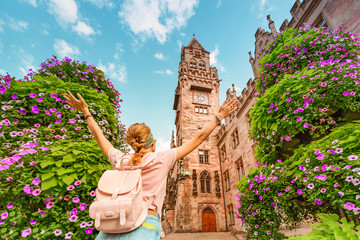 A girl traveler enjoys a view of the town hall building in Saarbrücken. Travel in Germany concept