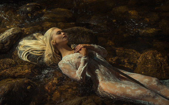 woman lying on the river, the legend of lady of the lake, beautiful woman with sword in white lace underwear, fantasy image