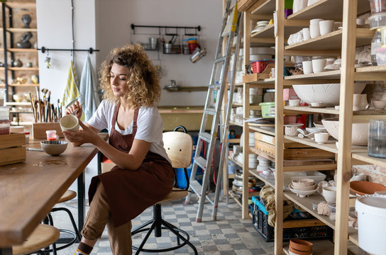 Craftswoman painting a bowl made of clay in art studio