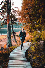 Backview of a adventure blonde active girl walking on a wooden nature path in a beautiful healthy autumn landscape. Oderteich, Harz National Park in the Mountains, Germany