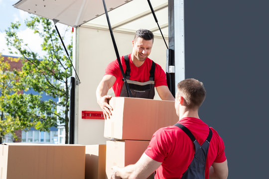 Two Male Worker Loading The Cardboard Boxes In Moving Truck