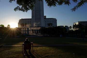 A homeless man sits in the morning sun eating breakfast at a park bench in front of  City Hall in downtown Los Angeles