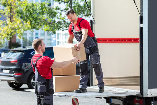 Two Young Male Movers Carrying Cardboard Boxes From Truck