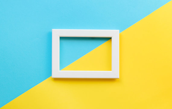 Mock up. White empty picture frame on multicolored blue and yellow paper background. Ukrainian or sweeden flag colors. Geometric. Bright trendy colors layout. Copy space. Abstract colourful texture.
