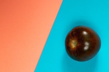 one ripe tomato on an orange-blue background of different varieties