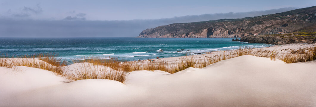 Panoramic costal view of Praia do Guincho Beach with Cresmina Dunes in foreground. Cascais, Portugal. Atlantic ocean spot for surfing, windsurfing and kitesurfing