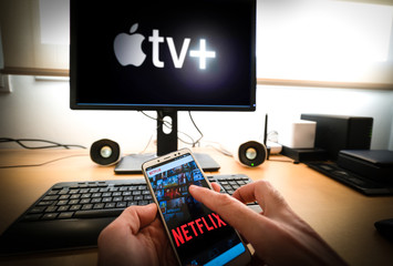 Barcelona, Spain. March 2019: Man holds a smartphone with netflix app and a Pc with the new Apple TVplus on screen