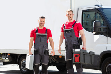 Portrait Of A Smiling Young Male Technicians Holding Tool Box