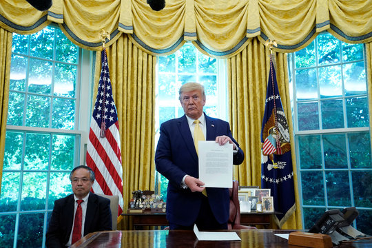U.S. President Trump holds letter from China's President Xi Jinping during meeting with China's Vice Premier Liu at the White House in Washington