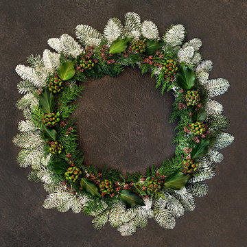 Natural winter and Christmas wreath with snow covered fir, ivy, and cedar leaves on brown grunge background.