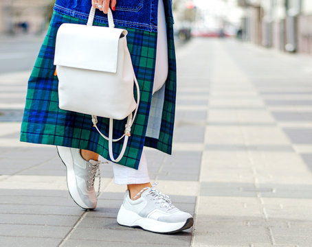 Fashionable bag close-up in female hands.Girl walks in the city outdoors. Stylish modern and feminine image, style. A woman in a raincoat, coat and with a white backpack. girl in sneakers and jeans.