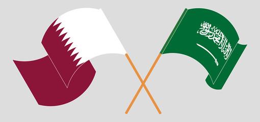 Crossed and waving flags of the Kingdom of Saudi Arabia and Qatar