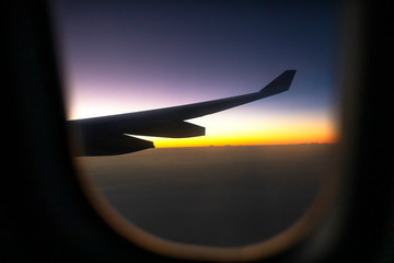 looking through plane window at colorful skyscape
