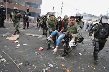 Military personnel assist a person during a protest against Ecuador's President Lenin Moreno's austerity measures in Quito, Ecuador