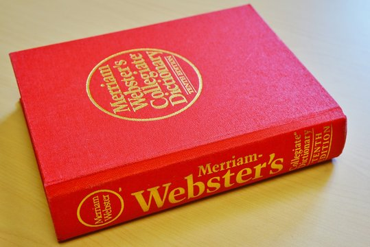 PRINCETON, NJ -11 OCT 2019- View of a Merriam Websters English dictionary with a red cover on a desk.