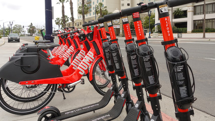 Dockless Jump electric scooters and bikes by Uber joint the fleet in downtown San Diego. Photo taken in San Diego, CA / USA on May 2, 2019.