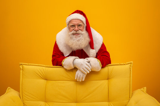 Santa Claus sitting on a yellow couch on yellow background with copy space. Yellow sofa.