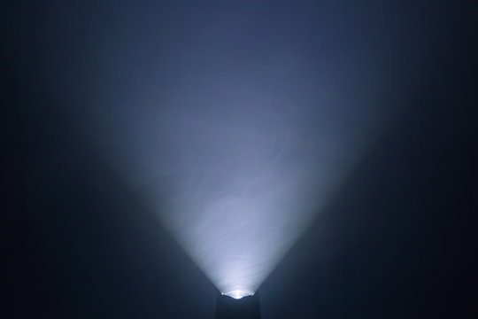 flashlight and light beam in dark mist room at night . abstract projector spotlight white lay growing .