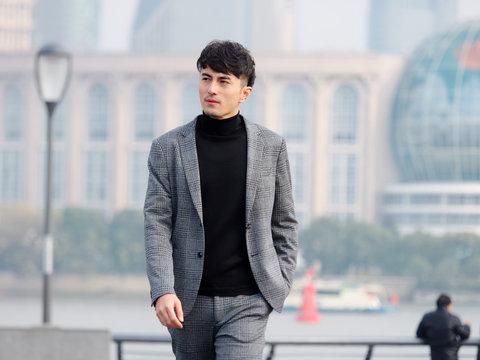 Confident and handsome Chinese young business man in casual suit walking outdoor with hand in his pocket against Shanghai bund background, Chinese businessman lifestyle concept.