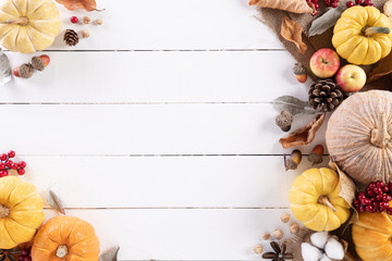 Top view of Autumn maple leaves with Pumpkin and red berries on white wooden background....