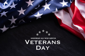 Happy Veterans Day. American flags with the text thank you veterans against a blackboard background. November 11.