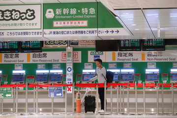 A man stands in front of ticket machines in Tokyo Station after Shinkansen bullet train services were suspended due to Typhoon Hagibis according to the operators, in Tokyo