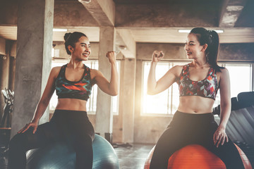 Two women in sportswear workout at the gym, cinematic tone Fototapete