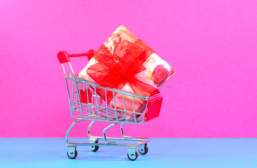 Shopping cart with gift on a pink background
