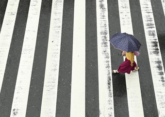 A woman walks in the rain at a pedestrian crossing near Osaka Station as Typhoon Hagibis approaches Osaka