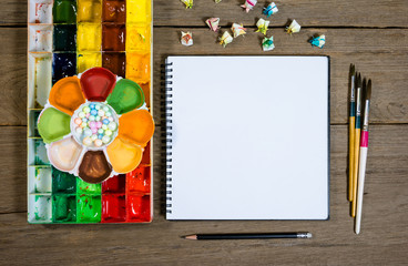 closeup open note book with tray colors on wood background