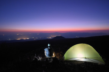 Hiker Overlooking Town Lights From Wild Camp At Twilight