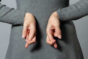 Liar concept. Woman talking untruth and holding her fingers crossed behind her back.