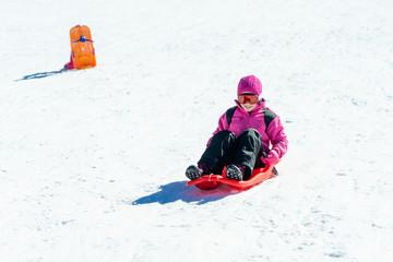 Little girl sledding at Sierra Nevada ski resort.