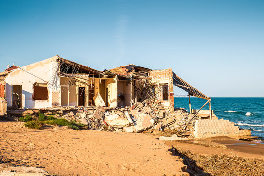 ruined house on the beach after a storm due to strong waves. Climate change