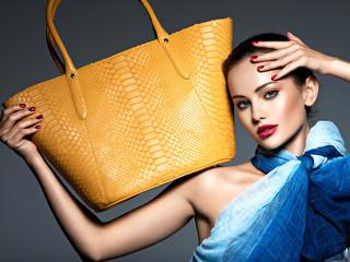 Stylish beautiful  woman wearing blue scarf  with yellow handbag Wall mural
