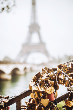 Locks of couples in love hang on metal bars on the background of the Eiffel tower Paris