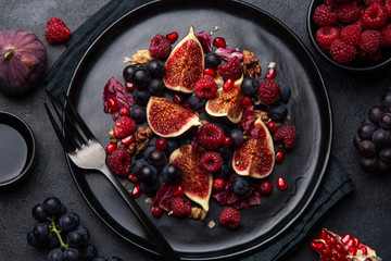 Fruit fig, grape, raspberry and pomegranate salad on black plate