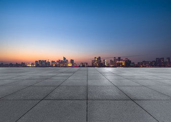 Fotomurales - Panoramic skyline and buildings with empty square floor at dusk