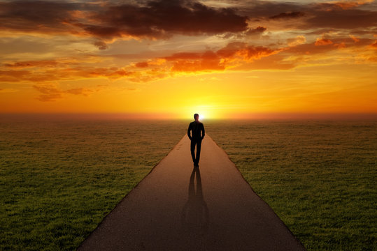 Man walking alone on a road towards the sunset