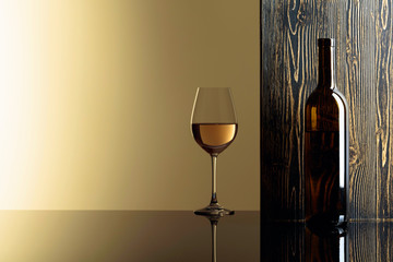 Bottle and glass of white wine on a black table.