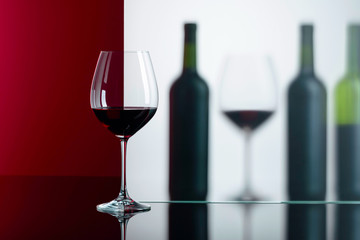Bottles and glasses of red wine on a black reflective background.