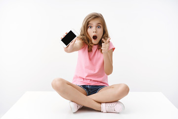Amazed excited european blond teenage girl ambushed, sit crossed legs, shaking smartphone showing mobile phone screen pointing display, open mouth wondered and impressed, share cool awesome game
