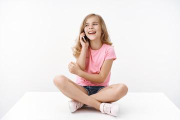 Cheerful carefree happy blond european teenage little girl having funny amusing conversation, sit relaxed crossed legs on floor, talking smartphone laughing joyfully, pose white background